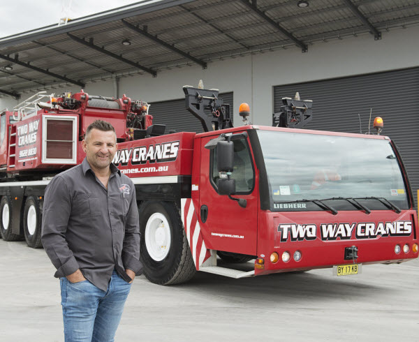 Man standing with Red crane behind him