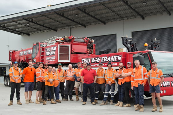 Group of men in front of a big red crane