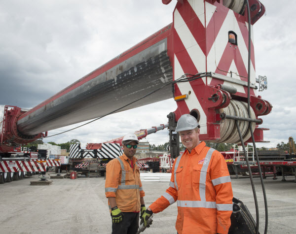 Two men standing next to two way crane