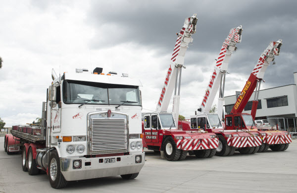 Red cranes and a truck parked outside the warehouse